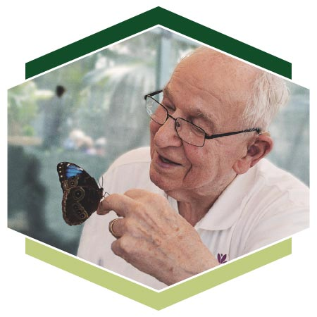 Resident handling butterfly at nature conservatory
